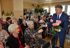 Artur Domański Departament Promocji, Sportu i Turystyki wręczający kwiaty kobietom.