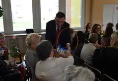 Poseł na Sejm RP Kazimierz Choma wręczający czekolady kobietom.