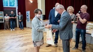 Starosta Kraśnicki Andrzej Rolla wręcza nagrodę uczestniczce konkursu fotograficznego .