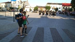 dzieci wybierające się na grę w piłkę z zaciekawieniem obserwowały wydarzenie na rynku