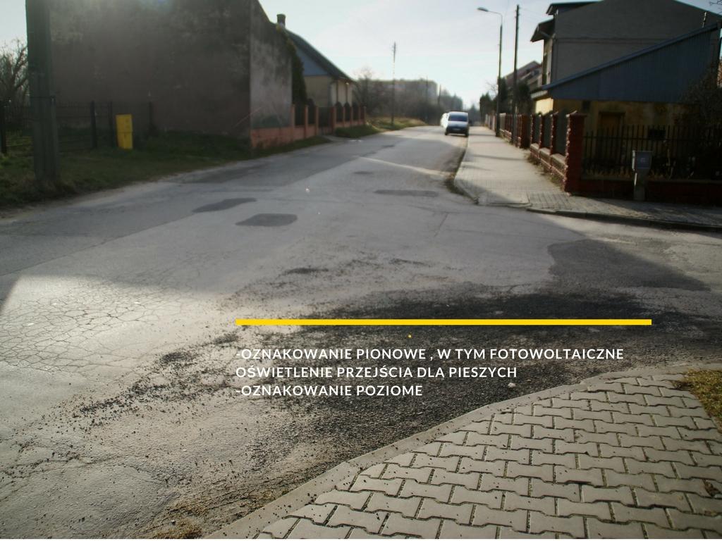 zdjęcie drogi z napisem: -oznakowanie pionowe , w tym fotowoltaiczne oświetlenie przejścia dla pieszych -oznakowanie poziome