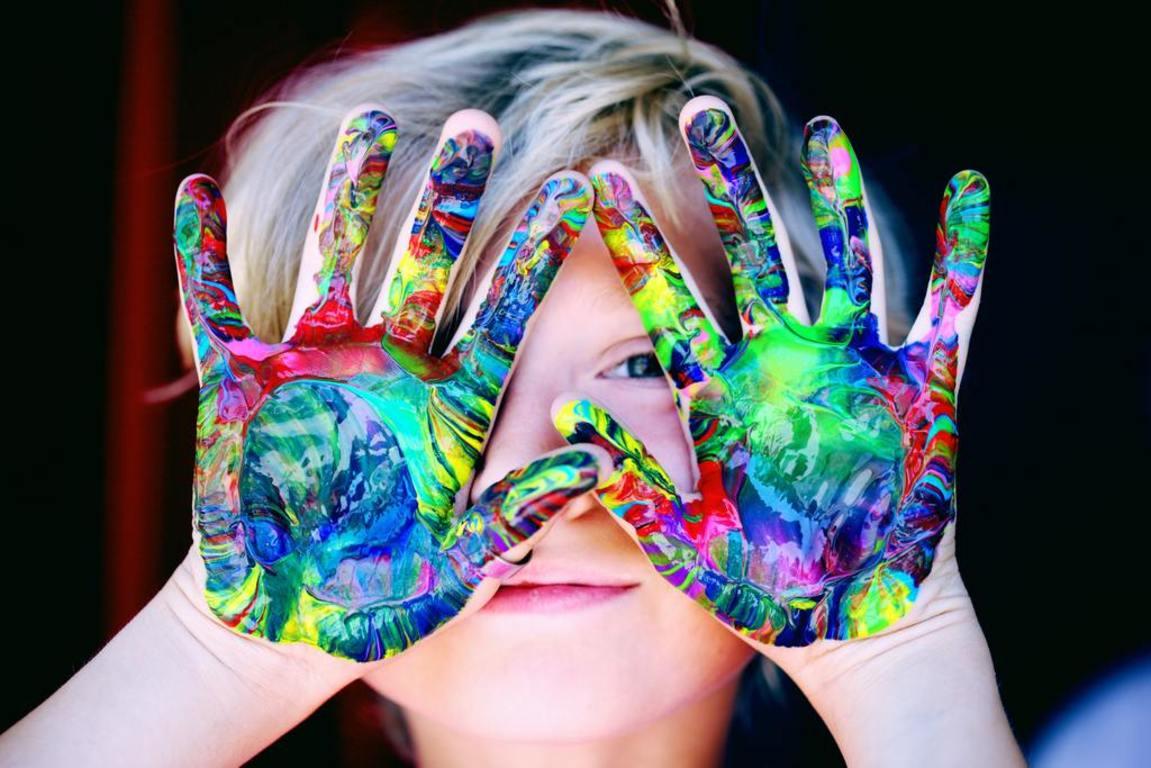 zdjęcie przedstawiające dziecko z dłońmi pomalowanymi kolorowymi farbami