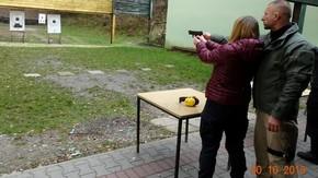 uczennica z pomocą instruktora oddaje strzał do tarczy pistoletem