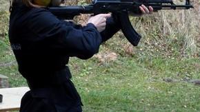 uczennica mierzy w tarczę karabinem maszynowym