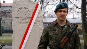 tablica pamiątkowa i stojący przy niej strzelec