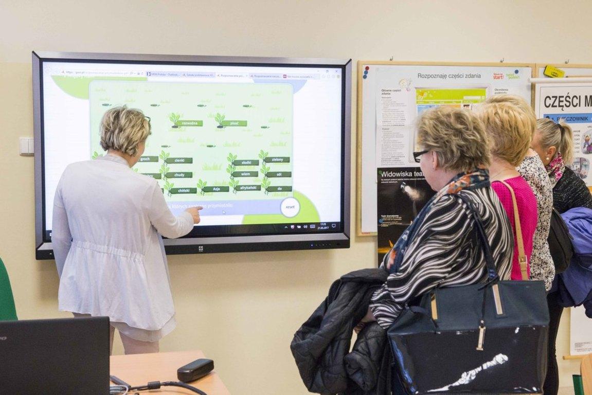 Nauczyciel pokazuje rodzicom działanie tablicy multimedialnej.
